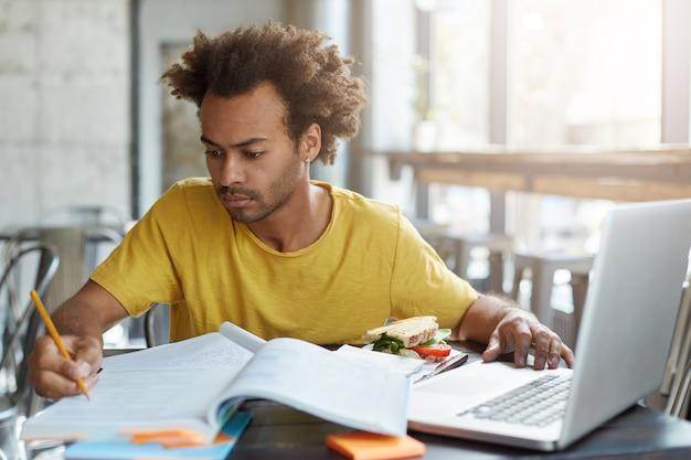Ernstige zelfverzekerde jonge donkere leraar in vrijetijdskleding bezig met onderwijsplan, notities maken met pen, zittend aan kantine met schoolboeken, schrijfboeken, notebook pc en sandwich op tafel