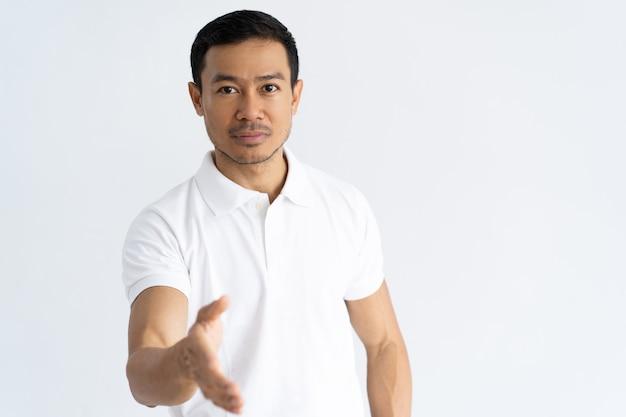 Ernstige zelfverzekerde kerel die handdruk aanbiedt