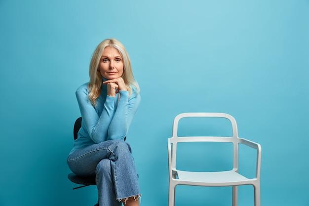Ernstige zelfverzekerde volwassen europese vrouw kijkt direct, houdt handen onder kin ontspant op stoel