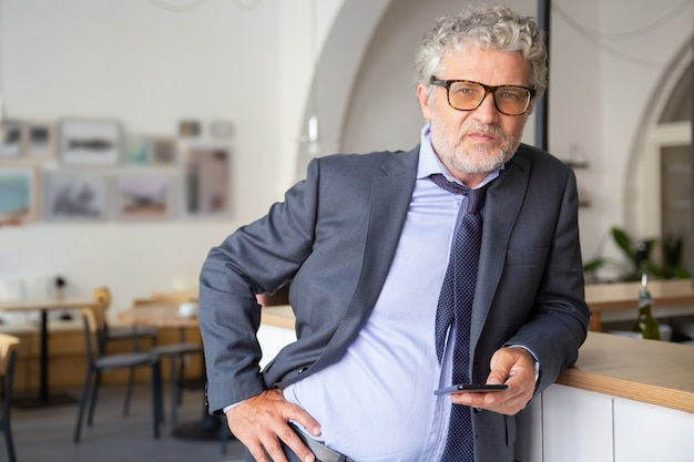 Ernstige zelfverzekerde volwassen zakenman bril en pak, met behulp van smartphone, permanent in co-werkruimte