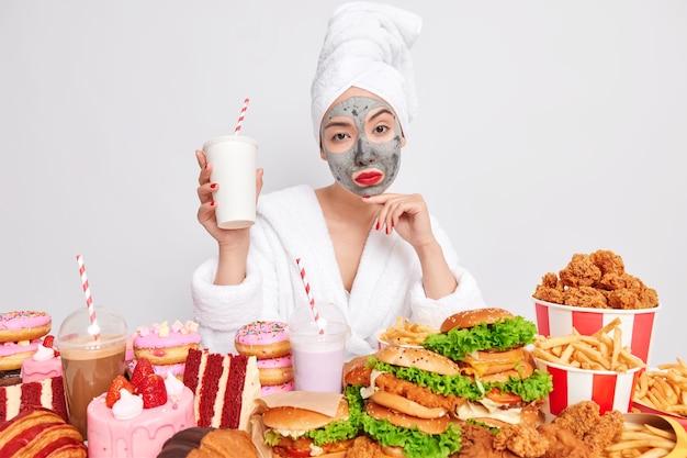 Ernstige zelfverzekerde vrouw kijkt serieus naar de camera omringd door fastfood