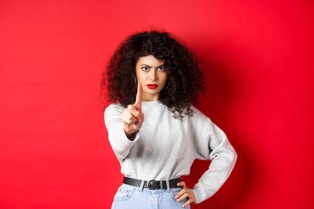 Ernstige zelfverzekerde vrouw zegt nee, steek een vinger uit om je te stoppen, verbied iets slechts, staand vastbesloten tegen een rode achtergrond.