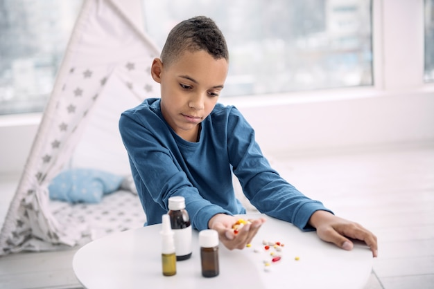 Ernstige ziekte. boos afro-amerikaanse jongen met drugs terwijl hij naar beneden staarde