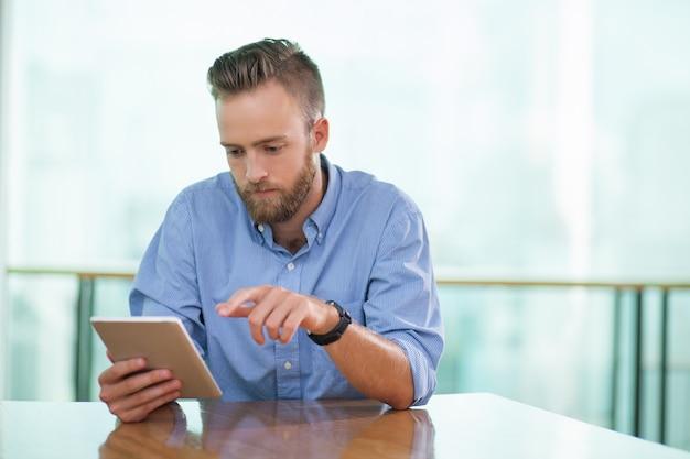 Ernstige zitting van de mens in cafe tafel en tablet met behulp van