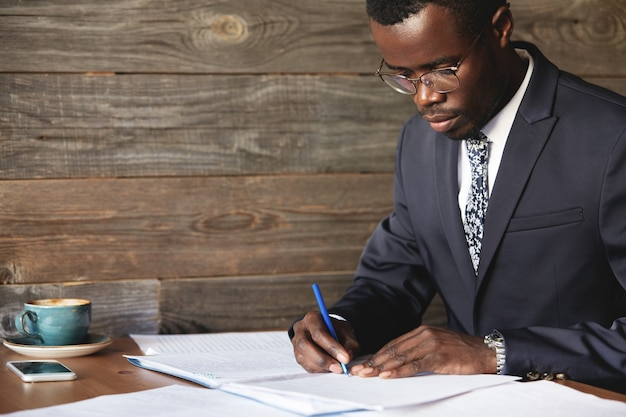 Ernstige zwarte bedrijfsmedewerker in formeel pak en bril die een lucratief contract ondertekent