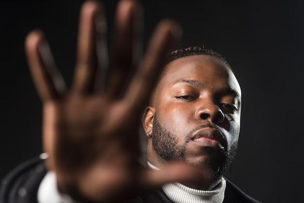 Ernstige zwarte man die je zegt te stoppen met een open hand. detailopname. zwarte achtergrond.