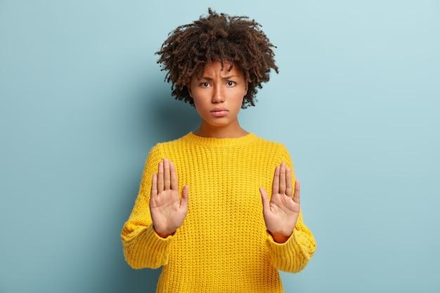 Ernstige zwarte vrouw met norse uitdrukking houdt de handpalmen vooraan, maakt stopgebaar, weigert iets, kijkt ontevreden