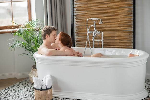 Erotische momenten. een man en een vrouw die samen in bad gaan en er opgewonden uitzien