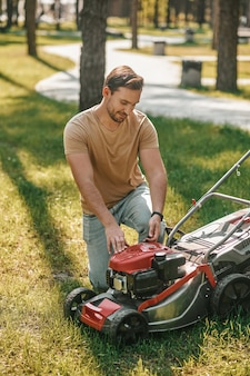 Ervaar een zelfverzekerde glimlachende man in een licht t-shirt, gehurkt en een grasmaaier op groen gazon aangeraakt