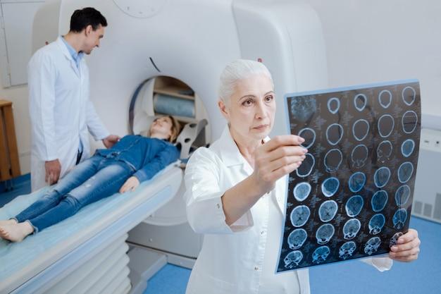 Ervaren aardige oude arts die naar de röntgenfoto kijkt en nadenkt over de diagnose terwijl hij in het ct-lab staat