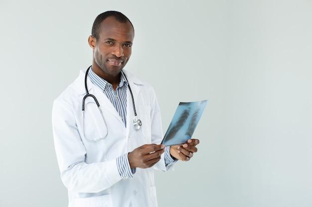 Ervaren afro-amerikaanse arts die röntgenscan houdt terwijl hij tegen een witte muur staat