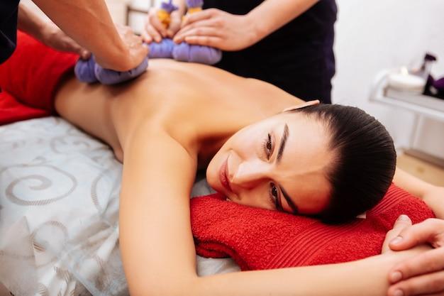 Ervaren arbeiders. aangename, gedeeltelijk naakte vrouw die op de buik ligt tijdens een ontspannende sessie terwijl ze haar rug verwerkt