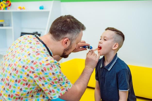 Ervaren arts bekijkt jongenskeel met speciale instrumenten in kliniek. kinderarts in medisch uniform onderzoekt keel klein kind.