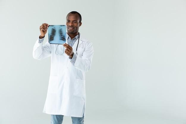 Ervaren arts die een röntgenfoto vasthoudt tijdens het maken van een analyse