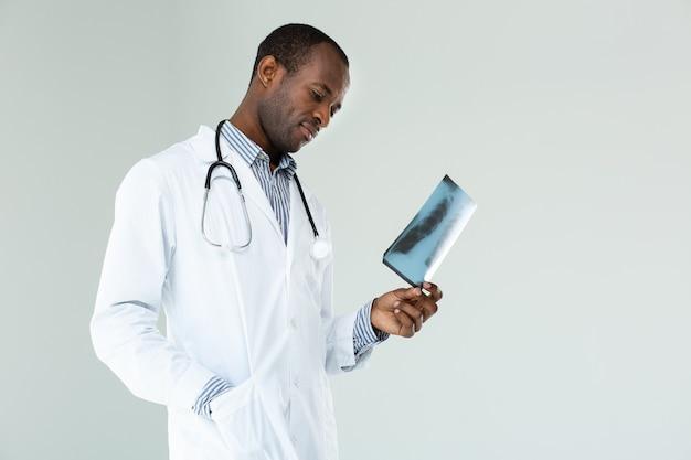 Ervaren arts die zich tegen een witte muur bevindt terwijl hij röntgenscan vasthoudt