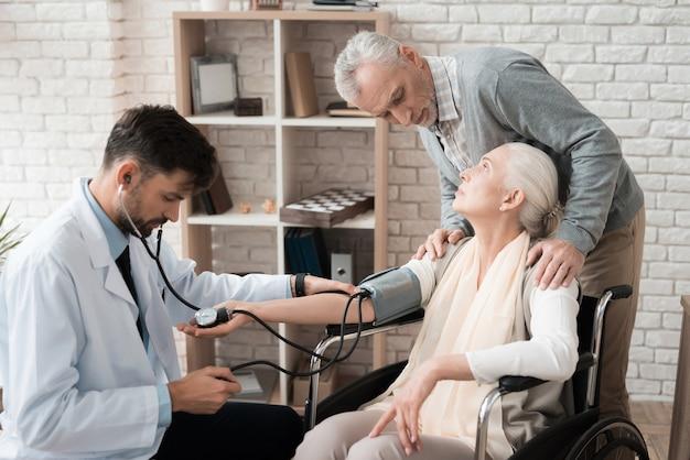 Ervaren arts met tonometer helpt oude vrouw.