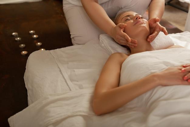 Ervaren bewegingen. mooie onberispelijke dame liggend op een overdekte matras en een aangename massage ontvangen terwijl ze ontspannen is
