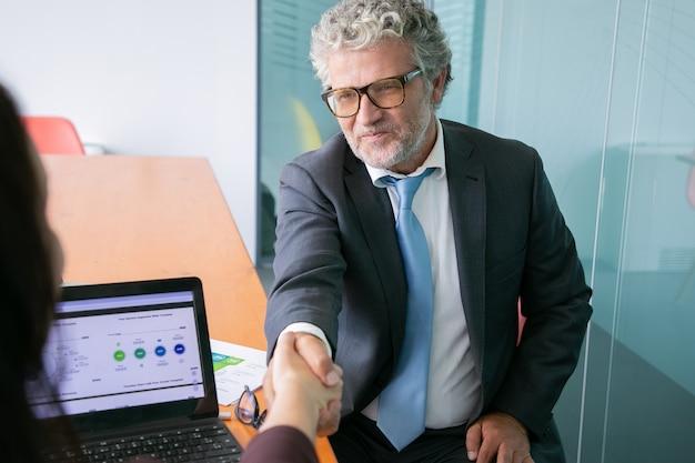 Ervaren blanke zakenman handshaking en glimlachen