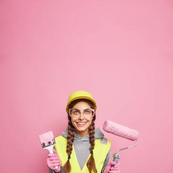 Ervaren bouwer voert bouwonderhoud uit, reparatie- en verbouwingswerkzaamheden houdt bouwgereedschap voor het opknappen van muren in appartement draagt veiligheidskleding geïsoleerd op roze muur