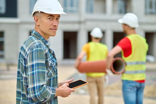 Ervaren bouwmanager en twee laders met een afvoerleiding