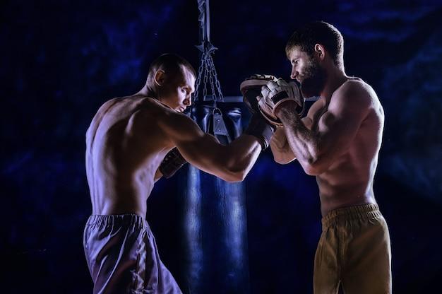 Ervaren coach bereidt een jonge vechter voor. de jager oefent de onderste zijdelingse botsing uit en de coach staat met de voering van de arm