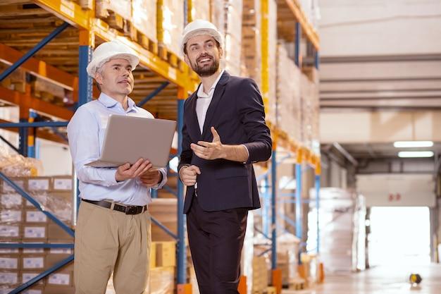 Ervaren collega's. blije slimme managers die glimlachen terwijl ze met elkaar praten over werk