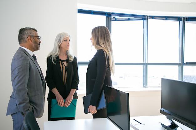 Ervaren collega's staan in kantoorruimte en kijken elkaar aan. professionele inhoud ceo en mooie zakenvrouwen die werkproject bespreken. bedrijfs-, communicatie- en corporatieconcept