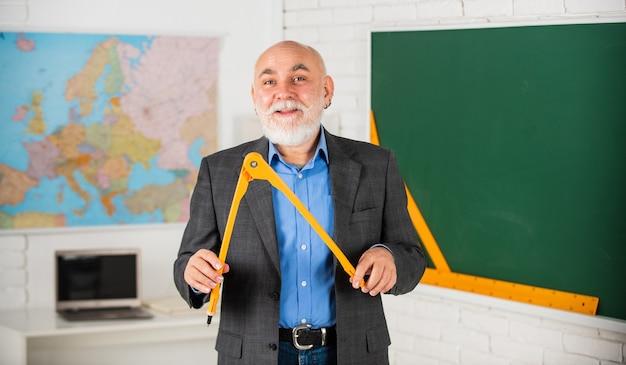 Ervaren docent. rijpe leraar geniet van lesgeven. stam onderwerpen. laat het me uitleggen. op maat gemaakte leerervaringen. senior intelligente man leraar op schoolbord. leraar old school generatie.