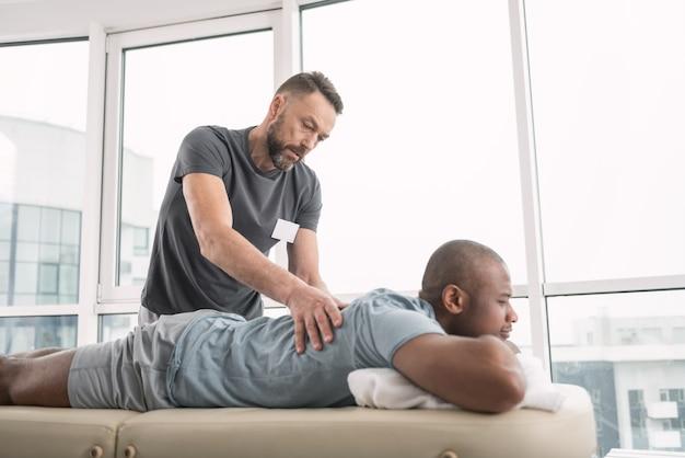 Ervaren dokter. ernstige bekwame man die de rug van zijn patiënten bekijkt terwijl hij een professionele massage doet