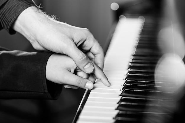 Ervaren hand van de oude muziekleraar helpt de kindleerling
