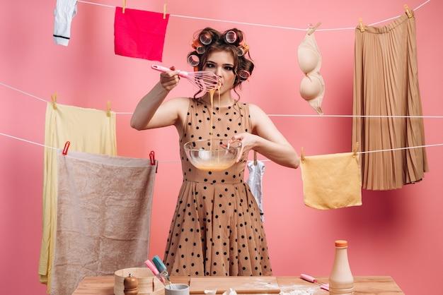 Ervaren huisvrouw controleert of het ei klaar is. leuk meisje in een bolletjesjurk bereidt voedsel op een roze niveau.