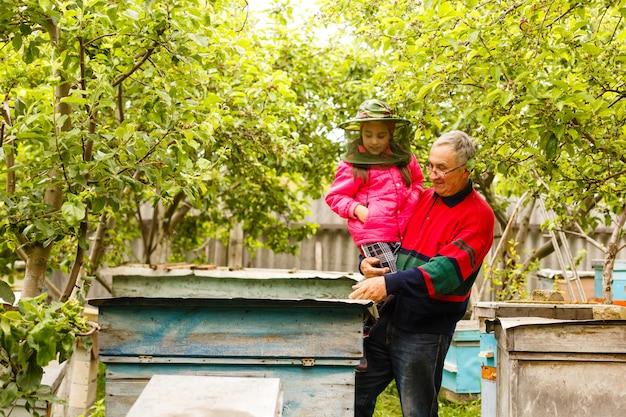 Ervaren imker-grootvader leert zijn kleindochter voor de verzorging van bijen
