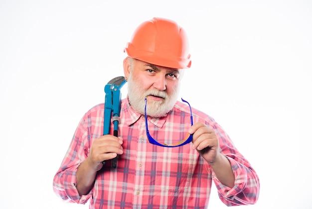 Ervaren ingenieur. verbouwing. loodgieter dienst. man bebaarde loodgieter draagt een helm en houdt moersleutelgereedschap vast. reparatieconcept. sanitaire techniek. loodgieter werkplaats. loodgieter repareren of renoveren.