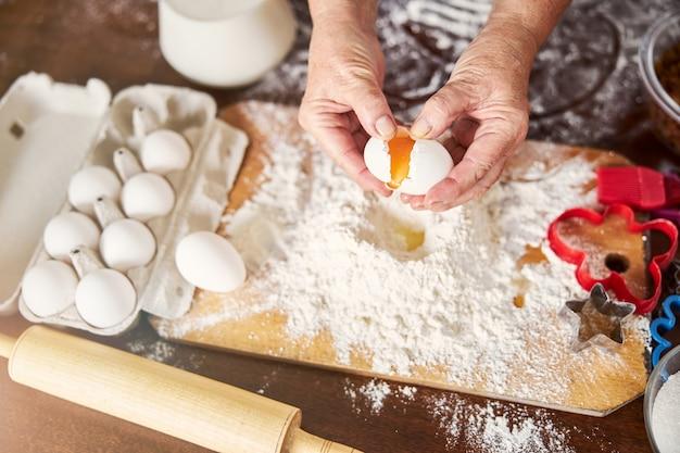 Ervaren kok die een ei toevoegt aan een stapel bloem