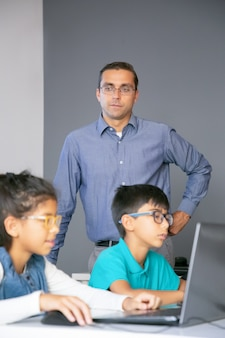 Ervaren leraar van middelbare leeftijd die naar studenten kijkt