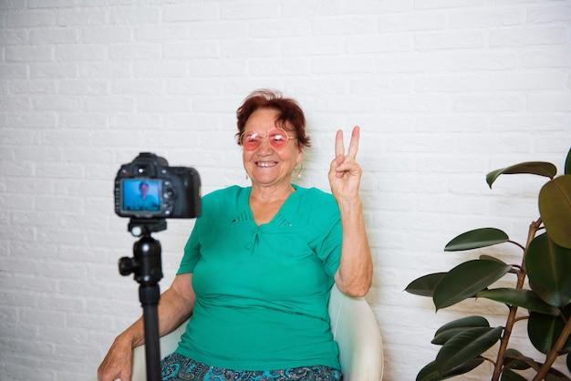 Ervaren life coach. vriendelijke senior vrouw blogger zittend op de bank en video-vlog thuis opnemen