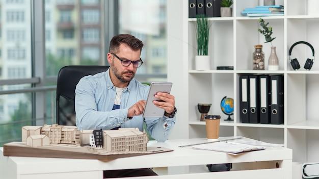 Ervaren mannelijke architect op kantoor inspecteert het project van een wooncomplex en maakt berekeningen met behulp van een tablet-pc.