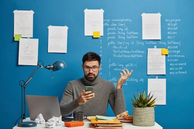 Ervaren mannelijke programmeur of it-projectmanager probeert probleem op te lossen met moderne technologieën, houdt de hand opgestoken