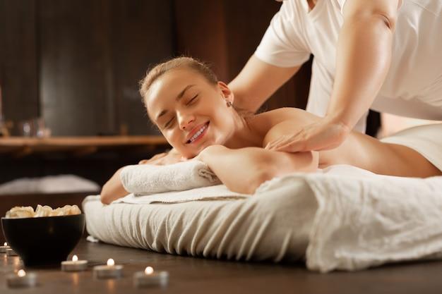Ervaren massagemeester. stralende blonde vrouw die in een goed humeur is tijdens massagesessie terwijl bekwame meester op haar lichaam drukt