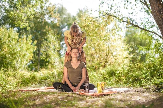 Ervaren masseuse geeft haar cliënt een verfrissende massage in het zonlicht