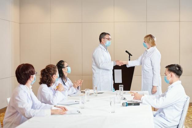 Ervaren onderzoekers met medische maskers die handen schudden na een succesvolle medische conferentie gewijd aan coronavirus