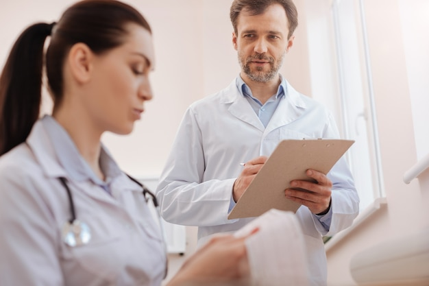 Ervaren onzekere slimme cardioloog die zijn collega-arts vraagt om de cardiogramopname te bekijken terwijl hij de diagnose uitzoekt