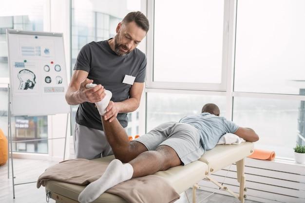 Ervaren orthopeed. aardige bekwame man die naar de voeten van zijn patiënt kijkt terwijl hij zijn been vasthoudt