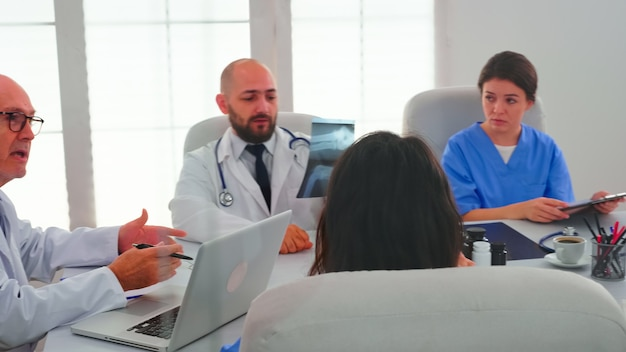 Ervaren oudere artsen in de vergaderruimte van het ziekenhuis werken samen met een medisch team tijdens het gezondheidsseminar. kliniekdeskundige therapeut in gesprek met collega's over ziekte, medisch professional