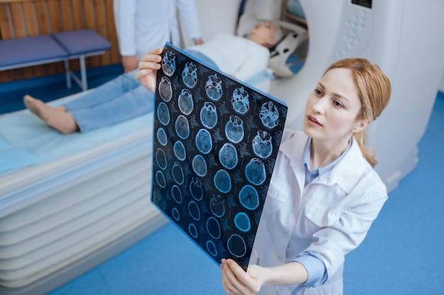 Ervaren professionele vrouwelijke oncoloog die de resultaten van de mri-scan bekijkt en nadenkt over de diagnose terwijl hij in het medische laboratorium staat