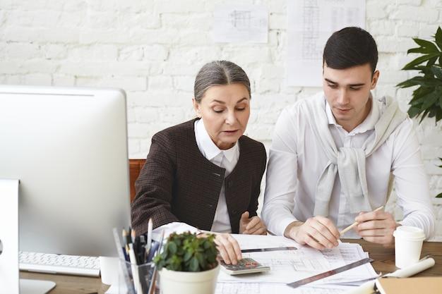 Ervaren rijpe vrouw architect met grijze haren zittend op haar werkplek met jonge gerichte man assistent herziening van tekeningen en projectdocumentatie, rekenmachine gebruiken om metingen te controleren