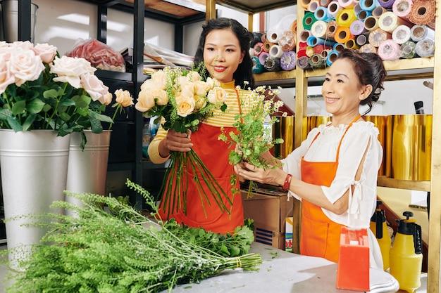 Ervaren senior bloemist die een beginner leert hoe je bloemen in een prachtig boeket kunt plaatsen