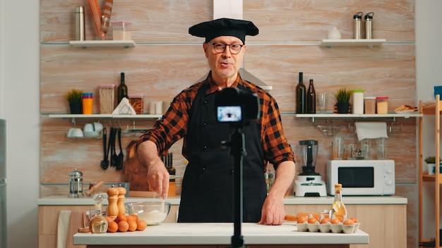Ervaren senior chef-kok opname tutorial met voedselbereiding in de keuken. gepensioneerde blogger-beïnvloeder die internettechnologie gebruikt om te communiceren over bloggen op sociale media met digitale apparatuur