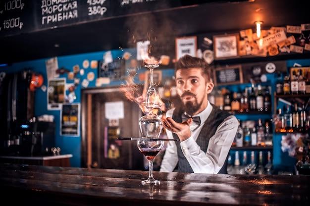 Ervaren tapster maakt een show en creëert een cocktail in de nachtclub