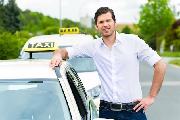 Ervaren taxichauffeur voor zijn taxi, wachtend op een passagier